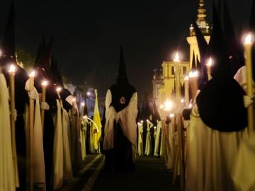Un grupo de nazarenos en una procesión de la Semana Santa de Sevilla